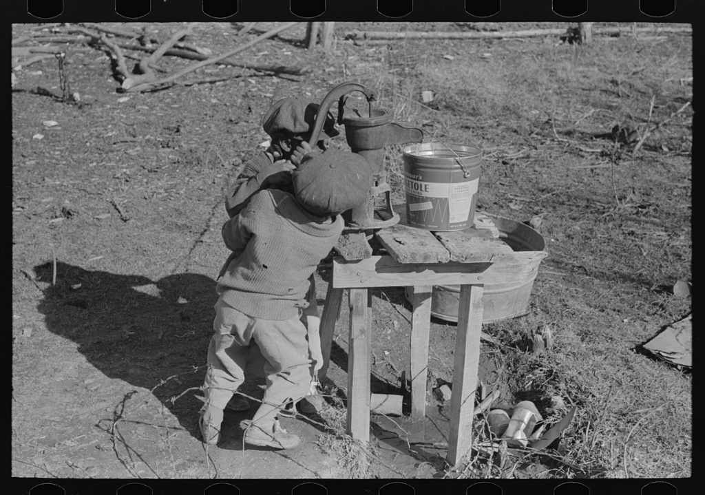 """Library of Congress Photo: """"Children of Negro sharecropper pumping water. Family will be resettled at Transylvania Project, Louisiana"""""""