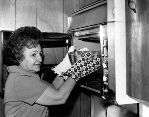Ella Rita Helfrich, second place winner in the 1966 Pillsbury Bake-Off, places a bundt pan with her prize-winning Tunnel of Fudge cake in the oven.